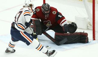 Edmonton Oilers center Connor McDavid (97) slides the puck between the legs of Arizona Coyotes goaltender Adin Hill (31) for a goal during the second period of an NHL hockey game Wednesday, Jan. 2, 2019, in Glendale, Ariz. (AP Photo/Ross D. Franklin)