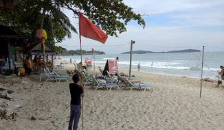 A man raises a red flag indicating rough weather conditions in Chaweng beach, Koh Samui, Thailand, Thursday, Jan. 3, 2019. Thai weather authorities are warning that a tropical storm will bring heavy rains and high seas to southern Thailand and its famed beach resorts. (AP Photo/Sithipong Charoenjai)