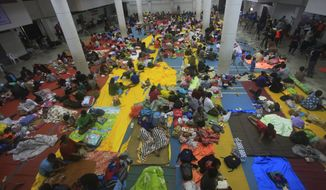 Thai people sleep at an evacuation center in Nakhon Si Thammarat province, Thailand, Thursday, Jan. 3, 2019. Thai weather authorities are warning that a tropical storm will bring heavy rain and high seas to southern Thailand and its famed beach resorts. (AP Photo/Sumeth Panpetch)