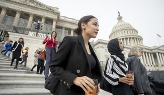 Rep. Alexandria Ocasio-Cortez, D-N.Y., center, Rep. Ilhan Omar, D-Minn., second from right, and others walk down the House steps to take a group photograph of the House Democratic women members of the 116th Congress on the East Front Capitol Plaza on Capitol Hill in Washington, Friday, Jan. 4, 2019, as the 116th Congress begins. (AP Photo/Andrew Harnik)