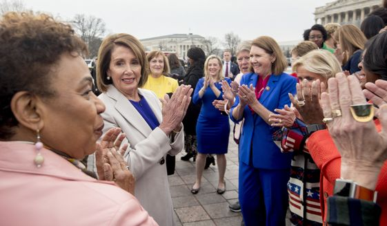 House Speaker Nancy Pelosi of Calif., second from left, applauds after a group portrait of the House Democratic women members of the 116th Congress on the East Front Capitol Plaza Capitol Hill in Washington, Friday, Jan. 4, 2019, as the 116th Congress begins. Also pictured is Rep. Barbara Lee, D-Calif., left. (AP Photo/Andrew Harnik)