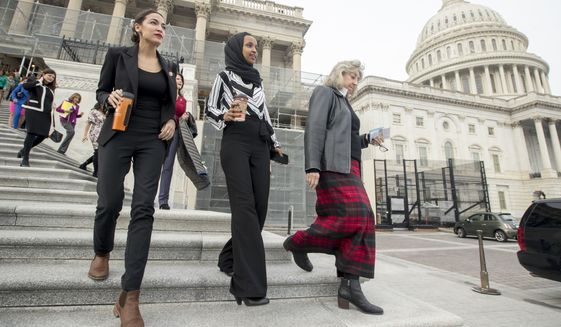 Rep. Alexandria Ocasio-Cortez, D-N.Y., left, and Rep. Ilhan Omar, D-Minn., second from left, walk down the House steps to take a group photograph of the House Democratic women members of the 116th Congress on the East Front Capitol Plaza on Capitol Hill in Washington, Friday, Jan. 4, 2019, as the 116th Congress begins. (AP Photo/Andrew Harnik)