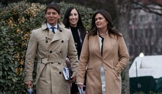 White House press secretary Sarah Huckabee Sanders walks with deputy press secretary Hogan Gidley to speak with reporters about the government shutdown outside the White House, Friday, Jan. 4, 2019, in Washington. (AP Photo/Evan Vucci)