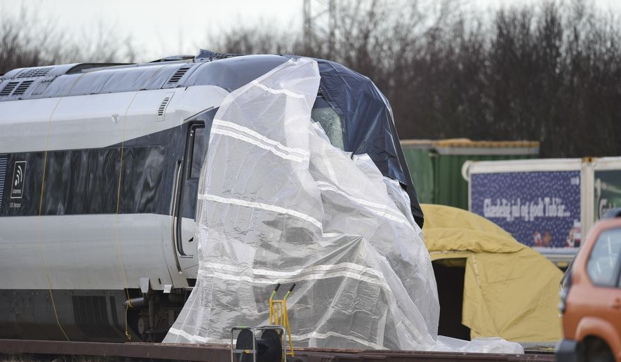 The train involved in the Wednesday morning accident is covered in Nyborg, Denmark, Thursday Jan. 3, 2019. Two more bodies have been found in the wreckage of a train crash on a Danish bridge, raising the death toll to eight in Denmark's deadliest train accident in 30 years, police said Thursday. (Mads Claus Rasmussen/Ritzau Scanpix via AP)