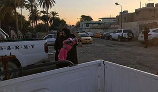 People gather outside a women's shelter to check on their relatives after a fire in Baghdad, Iraq, Friday, Jan. 4, 2019. The fire killed several lodgers, according to police, who gave conflicting accounts of the tragedy. (AP Photo/Ali Abdul Hassan)
