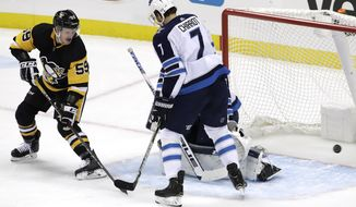 Pittsburgh Penguins' Jake Guentzel (59) watches as a shot from the point by Olli Maatta (3) gets past Winnipeg Jets goaltender Connor Hellebuyck, rear, and Ben Chiarot (7) during the first period of an NHL hockey game in Pittsburgh, Friday, Jan. 4, 2019. (AP Photo/Gene J. Puskar)