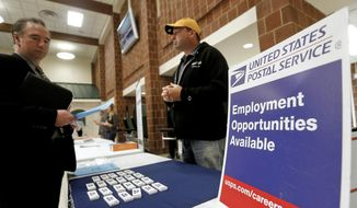 In this Nov. 2, 2017, file photo a recruiter from the postal service, right, speaks with an attendee of a job fair in the cafeteria of Deer Lakes High School in Cheswick, Pa. (AP Photo/Keith Srakocic, File)