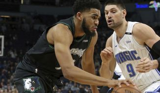 Minnesota Timberwolves' Karl-Anthony Towns, left, drives against Orlando Magic's Nikola Vucevic, of Montenegro, in the first half of an NBA basketball game Friday, Jan. 4, 2019, in Minneapolis. (AP Photo/Jim Mone)