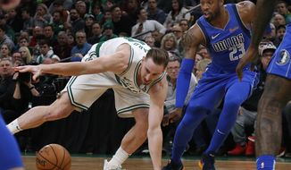 Boston Celtics forward Gordon Hayward (20) loses control of the ball next to Dallas Mavericks guard Wesley Matthews (23) during the first quarter of an NBA basketball game Friday, Jan. 4, 2019, in Boston. (AP Photo/Elise Amendola)