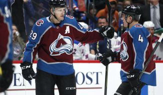 Colorado Avalanche center Nathan MacKinnon, left, is congratulated after scoring a goal by defenseman Tyson Barrie in the first period of an NHL hockey game against the New York Rangers Friday, Jan. 4, 2019, in Denver. (AP Photo/David Zalubowski)