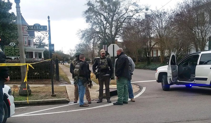 Lawmen gather at Mississippi University for Women in Columbus, Miss., Friday afternoon, Jan. 4, 2019, as they sweep the campus for an alleged gunman. The campus was placed on lockdown after reports of a shooting in front of Whitfield Hall, which houses Rent Auditorium. Police were searching the campus for a male suspect. Columbus Police Chief Fred Shelton confirmed there is one shooting victim, a male, at Baptist Memorial Hospital-Golden Triangle. (Isabelle Altman/The Commercial Dispatch via AP)