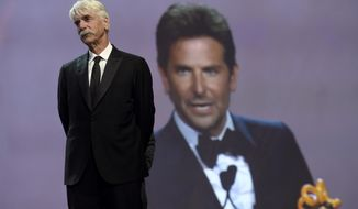 """Sam Elliott looks on as Bradley Cooper, seen in background screen, accepts the director of the year award for """"A Star Is Born"""" at the 30th annual Palm Springs International Film Festival on Thursday, Jan. 3, 2019, in Palm Springs, Calif. Looking on at right is (Photo by Chris Pizzello/Invision/AP)"""