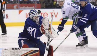 Toronto Maple Leafs goaltender Michael Hutchinson (30) makes a save as Toronto Maple Leafs defenseman Ron Hainsey (2) and Vancouver Canucks center Bo Horvat (53) look on during the second period of an NHL hockey game, Saturday, Jan. 5, 2019, in Toronto. (Nathan Denette/The Canadian Press via AP)