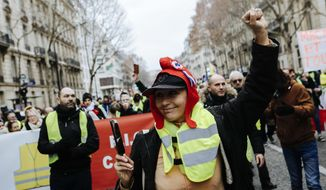 A yellow vest protester donning a red bonnet , that symbolizes the French Revolution during a march in Paris, Saturday, Jan. 5, 2019. Hundreds of protesters were trying to breathe new life into France's apparently waning yellow vest movement with marches in Paris and gatherings in other cities. (AP Photo/Kamil Zihnioglu)