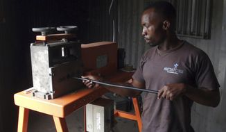 In this Nov. 26, 2018, photo, a man uses a wire-stripping machine to get to the copper and other metals in discarded electronic cables in Accra, Ghana. A safer option to burning the plastic coatings that fill lungfuls of acrid air, electrical cables are fed through the blades that slit open the plastic, making it easy to reach the copper or other metal wires inside. (AP Photo/Neil Shaw)