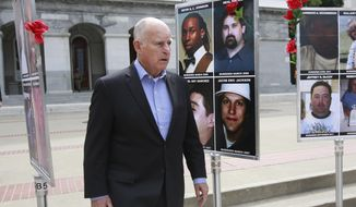 FILE - In this April 9, 2018 file photo, Gov. Jerry Brown walks past photos of murder victims displayed at the Capitol as he goes to address a victims' rights rally in Sacramento, Calif. The Democratic governor has spent much of his second two terms reducing criminal penalties and shuffling less-serious offenders to county jails instead of state lockups. (AP Photo/Rich Pedroncelli, File)