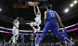 Philadelphia 76ers' Ben Simmons (25) hangs on the rim after a dunk as Jonah Bolden (43) and Dallas Mavericks' Luka Doncic (77) look on during the first half of an NBA basketball game, Saturday, Jan. 5, 2019, in Philadelphia. (AP Photo/Matt Slocum)