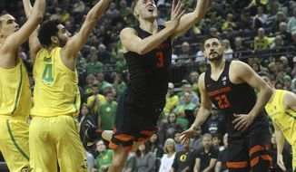 Oregon State's Tres Tinkle, center, goes up to shoot between Oregon's Paul White, left, Ehab Amin and teammate Gligorije Rakocevic, right, during the second half of an NCAA college basketball game Saturday, Jan. 5, 2019, in Eugene, Ore. (AP photo/Chris Pietsch)
