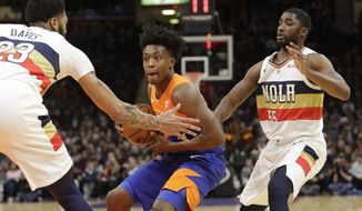 Cleveland Cavaliers' Collin Sexton, center, drives past New Orleans Pelicans' Anthony Davis, left, and E'Twaun Moore in the first half of an NBA basketball game, Saturday, Jan. 5, 2019, in Cleveland. (AP Photo/Tony Dejak)
