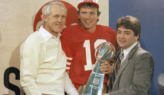 FILE - In this Jan. 20, 1985, file photo, San Francisco 49ers quarterback Joe Montana, center, holds the Lombardi Trophy with coach Bill Walsh, left, and 49ers owner Edward DeBartolo, Jr., in Stanford, Calif. There is no denying the impact on the coaching world that Walsh and Bill Parcells have had. The hard evidence is apparent again as the NFL playoffs begin. All 12 of the coaches have some sort of tie-in to either three-time Super Bowl champion Walsh or two-time winner Parcells. Yes, all 12. (AP Photo, File)