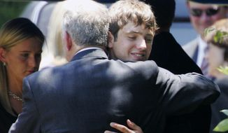 FILE - In this June 29, 2006, file photo, John Ramsey hugs his son, Burke, facing camera, at the graves of his wife, Patsy, and daughter JonBenet, during services for his wife at the St. James Episcopal Cemetery in Marietta, Ga. A $750 million defamation lawsuit filed against CBS by Burke Ramseu, the brother of JonBenet Ramsey, has been settled on Wednesday, Jan. 2, 2019. The Daily Camera reports court records show that a Michigan Circuit Court judge,  dismissed the lawsuit filed by Burke Ramsey in December 2016. (AP Photo/Ric Feld, File)