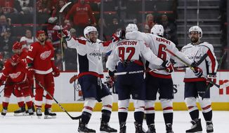 The Washington Capitals celebrate their third goal during the third period of an NHL hockey game against the Detroit Red Wings, Sunday, Jan. 6, 2019, in Detroit. (AP Photo/Carlos Osorio)