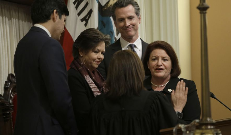 FILE- In this March 21, 2018 file photo, Lt. Gov. Gavin Newsom, second from right, watches as State Sen. Toni Atkins, D-San Diego, right, is sworn in as the new President Pro Tempore of the Senate by California Supreme Court Chief Justice Tani Cantil-Sakauye, second from right, at the Capitol, in Sacramento, Calif. Newsom,will be sworn-in to office Monday, Jan. 7, 2019, and will work with a Legislature firmly gripped by Democrats. (AP Photo/Rich Pedroncelli, File)