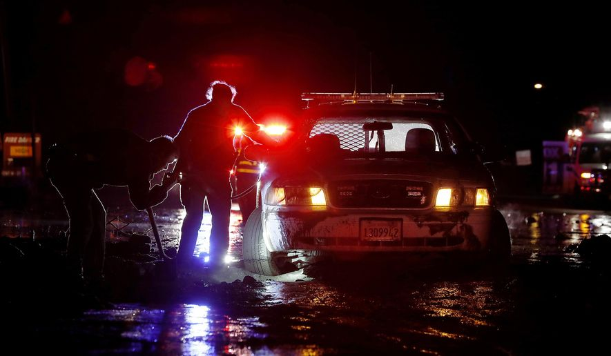 In this Saturday, Jan 5, 2019, photo sheriff's deputies work to free their patrol cruiser from mud covering a stretch of Pacific Coast Highway in Malibu, Calif. A winter storm unleashed mudslides in Southern California wildfire burn areas and trapped motorists on a major highway, and the northern part of the state is bracing for more wet weather. Saturday's deluge loosened hillsides in Malibu where a major fire burned last year, clogging the Pacific Coast Highway with mud and debris. (Luis Sinco/Los Angeles Times via AP)