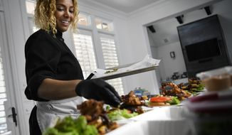 In this Friday, Nov. 2, 2018 photo, Chef Charity Morgan, wife of Tennessee Titans linebacker Derrick Morgan prepares vegan meals for about a dozen of her husband's teammates in Nashville, Tenn. Morgan not only cooks a plant-based diet for her family, she has established herself as a go-to vegan chef who creates culinary options good enough to satiate even a 280-pound tackle. (George Walker IV/The Tennessean via AP)