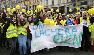 Women wearing yellow vests and holding yellow balloons march during a protest in Paris, Sunday, Jan. 6, 2019. Several hundred women wearing yellow vests march during a rally in Paris to give a different image to the movement. (AP Photo//Michel Euler)