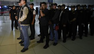 Prosecutors of the Guatemalan Attorney General's office take position inside the La Aurora International Airport in Guatemala City, late Saturday, Jan. 5, 2019. The Guatemalan government banned the entry of Yilen Osorio, an official of the International Commission Against Impunity in Guatemala (CICIG) and keeps it in the facilities of the La Aurora International Airport, despite the fact that the Constitutional Court ordered that they be granted visas and access to the members of the organism. (AP Photo/Santiago Billy)