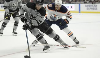 Los Angeles Kings center Anze Kopitar, center, takes the puck as Edmonton Oilers right wing Tobias Rieder loses his stick during the second period of an NHL hockey game, Saturday, Jan. 5, 2019, in Los Angeles. (AP Photo/Mark J. Terrill)