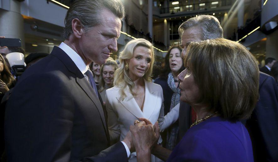 California Gov. Gavin Newsom, left, talks with U.S. House Speaker Nancy Pelosi, Monday, Jan. 7, 2019, in Sacramento, Calif. Newsom was sworn-in Monday as California's 40th governor. (AP Photo/Rich Pedroncelli)