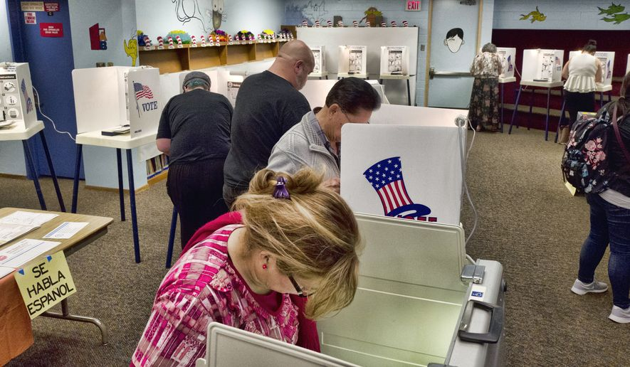 In this June 5, 2018, file photo, voters mark ballots at a polling place in the library at the Robert F. Kennedy Elementary School in Los Angeles. California's June primary saw the highest percentage of voter turnout in a midterm primary election since 1998. California Secretary of State Alex Padilla certified the results Friday, July 13, 2018.  (AP Photo/Richard Vogel, File)