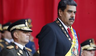FILE - In this  May 24, 2018 file photo, Venezuela's President Nicolas Maduro watches a military parade, alongside his Defense Minister Vladimir Padrino Lopez, behind, at Fort Tiuna in Caracas, Venezuela. State television in Venezuela showed President Maduro abruptly cutting short a speech on Saturday, Aug. 4, causing hundreds of soldiers present to break ranks and scatter.(AP Photo/Ariana Cubillos, File)