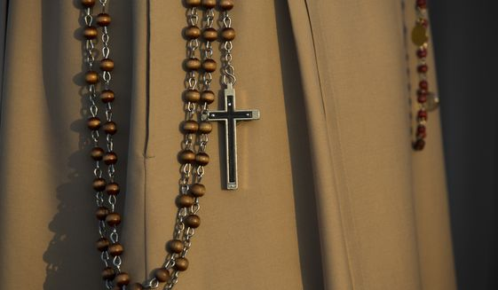 A nun holds a crucifix while waiting for the beginning of a beatification ceremony. (AP Photo/Santi Palacios) **FILE**