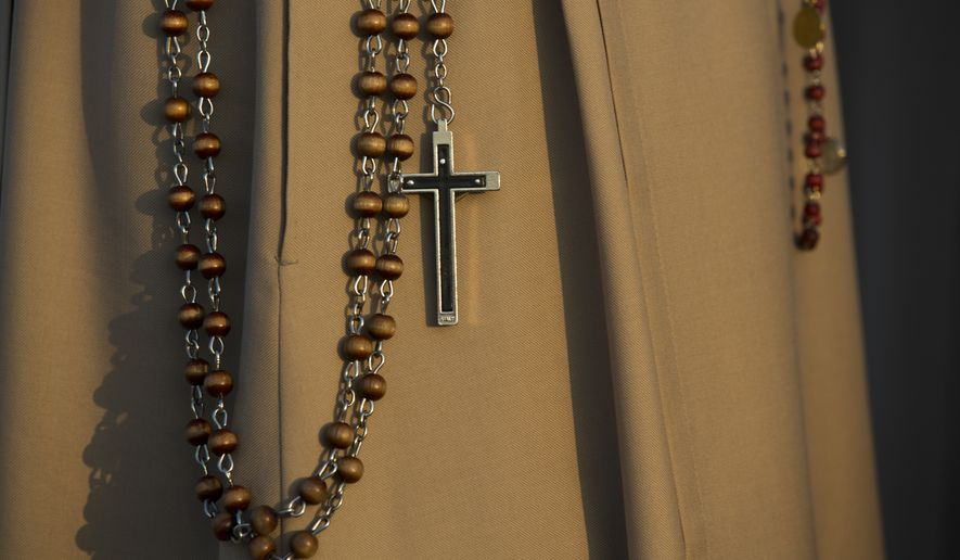A nun holds a crucifix while waiting for the beginning of a beatification ceremony. (AP Photo/Santi Palacios)