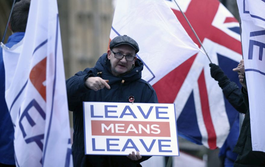 Pro-Brexit demonstrators wave flags and signs alongside anti-Brexit demonstrators, outside Parliament in London Monday Jan. 7, 2019. Parliament is expected to vote on Prime Minister Theresa May's Brexit withdrawal plan next week.  Monday January 7, 2019. (Yui Mok/PA via AP)