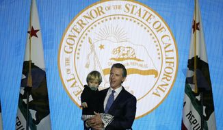 California Governor Gavin Newsom holds his son, Dutch, while speaking during his inauguration Monday, Jan. 7, 2019, in Sacramento, Calif. (AP Photo/Eric Risberg)