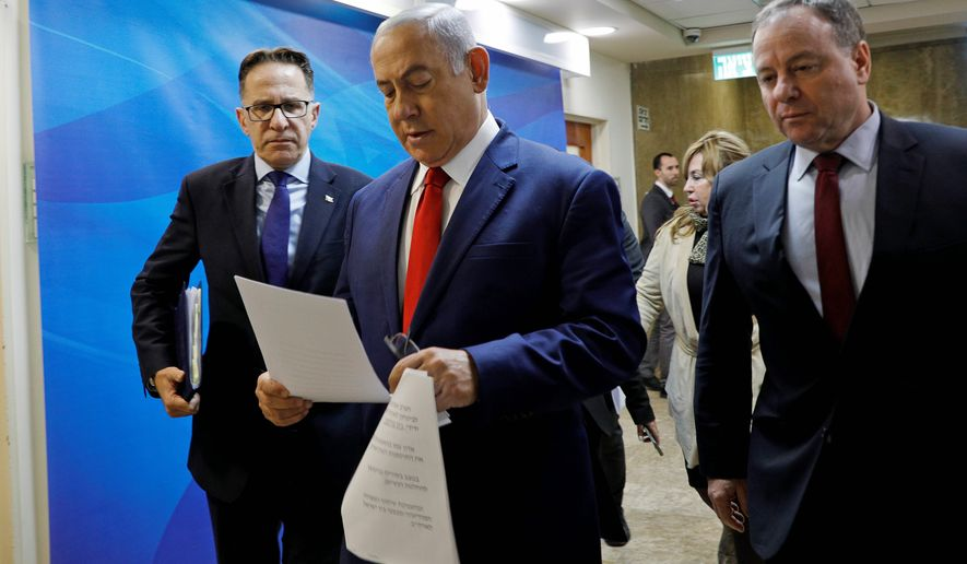 Israeli Prime Minister Benjamin Netanyahu reads a document as he arrives to the prime minister's office for the weekly cabinet meeting, in Jerusalem, Sunday, Jan. 6, 2019. (Gali Tibbon/Pool via AP)