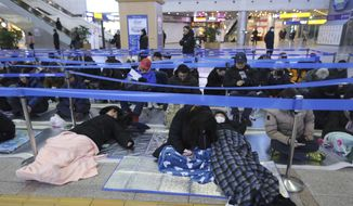 People sleep as they wait to buy train tickets for their hometown visits during Lunar New Year holidays at Seoul Railway Station in Seoul, South Korea, Tuesday, Jan. 8, 2019. South Koreans will visit their hometowns during a five-day holiday of the Lunar New Year which falls on Feb. 5 this year. (AP Photo/Ahn Young-joon) ** FILE **