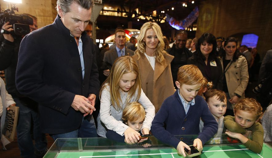 Governor-elect, Lt. Gov. Gavin Newsom, left, and his wife, Jennifer Siebel Newsom, center, watch last their children, daughter Montana, second from left, and sons, Dutch, foreground and Hunter, foreground fourth from left, operate robot games during an Inaugural Family Event at the California Railroad Museum, Sunday, Jan. 6, 2019,,Sacramento, Calif. Newsom will be sworn-in as California's 40th governor, Monday. (AP Photo/Rich Pedroncelli) Jennifer Siebel Newsom