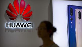 FILE - In this July 4, 2018, file photo, a shopper walks past a Huawei store at a shopping mall in Beijing. Chinese telecom equipment giant Huawei unveiled Monday, Jan. 7, 2019, a processor chip for data centers and cloud computing in a bid to expand into an emerging global market despite Western warnings the company might be a security risk. (AP Photo/Mark Schiefelbein, File)