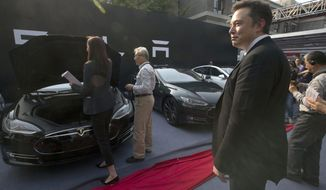 FILE - In this April 22, 2014, file photo. Tesla Motors CEO Elon Musk, right, looks on as a set of Tesla Model S sedans are delivered to its first customers in China at an event in Beijing. Musk said Monday, Jan. 7, 2019 on twitter that the automaker is breaking ground for a Shanghai factory and will start production of its Model 3 by the end of the year. (AP Photo/Ng Han Guan, File)