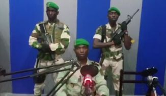 """In this image from TV, a soldier who identified himself as Lt. Obiang Ondo Kelly, commander of the Republican Guard, reads a statement on state television broadcast from Libreville, saying the military has seized control of the government, Monday Jan. 7, 2019. The statement said Soldiers from Gabon's Republican Guard have launched a coup """"to restore democracy"""" in the West African country, while imposing a curfew in the capital, and the internet has been cut.  No violence has been reported and President Ali Bongo has been out of the country since October amid reports that he had a stroke.(Gabon State TV via AP)"""