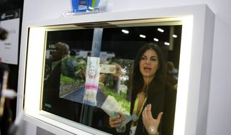 A woman demonstrates the Artemis smart mirror at the CareOS booth during CES Unveiled at CES International, Sunday, Jan. 6, 2019, in Las Vegas. The interactive mirror has video capture, virtual try-ons, facial and object recognition, and can give the user video instruction on specific makeup products, among other things. (AP Photo/John Locher) **FILE**