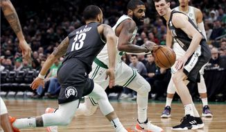 Boston Celtics guard Kyrie Irving, center, drives between Brooklyn Nets guard Shabazz Napier (13) and forward Rodions Kurucs (00) during the second half of an NBA basketball game in Boston, Monday, Jan. 7, 2019. (AP Photo/Charles Krupa)
