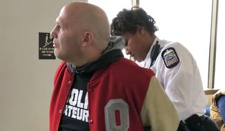 Mike DiSabato, left, turns himself in for arrest by an officer at Franklin County Municipal Court in Columbus, Ohio, on Monday, Jan. 7, 2019. DiSabato, whose claims helped spur the investigation into alleged, decades-old sexual abuse by an Ohio State team doctor, was jailed in a tangentially related telecommunications harassment case after missing a court date that he says he was misinformed about and never intended to skip. (AP Photo/Kantele Franko)