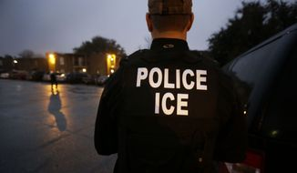 In this March 6, 2015, file photo, U.S. Immigration and Customs Enforcement agents enter an apartment complex looking for a specific undocumented immigrant convicted of a felony during an early morning operation in Dallas. (AP Photo/LM Otero, File) **FILE**