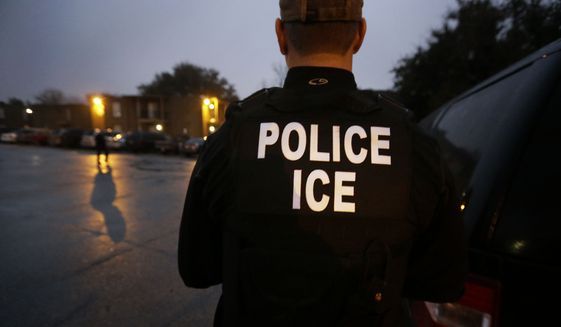 In this March 6, 2015, file photo, U.S. Immigration and Customs Enforcement agents enter an apartment complex looking for a specific undocumented immigrant convicted of a felony during an early morning operation in Dallas. (AP Photo/LM Otero, File)
